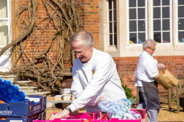 Chief Executive Edmund Newell working with chefs to pack food parcels