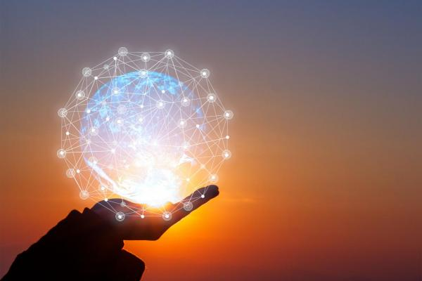 Image of a hand in silhouette, holding a glowing orb at sunset, representing human belief and ideas