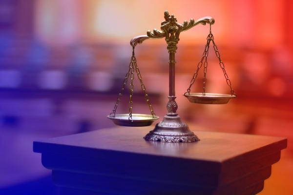 Composite image of the scales of justice, with a courtroom background