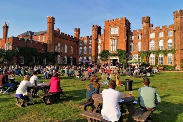 Guests watching 'Conference of the Birds' in the grounds of Cumberland Lodge