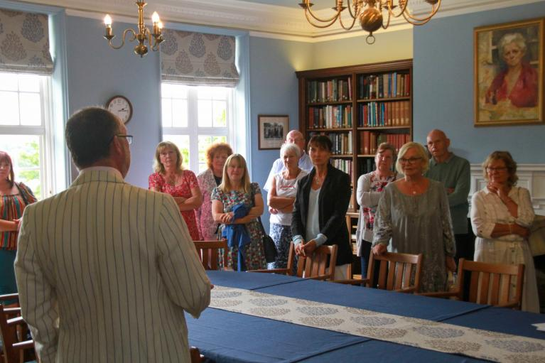 Photo of guests taking part in a guided tour of Cumberland Lodge, visiting the Amy Buller Library